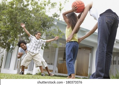 Happy family having fun outside with a basketball.