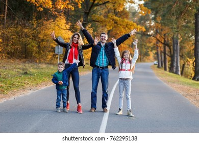 A happy family having fun in the park in autumn walking and hugging. Family, love, happiness concept. Family of four with mother father sister and a little cute brother