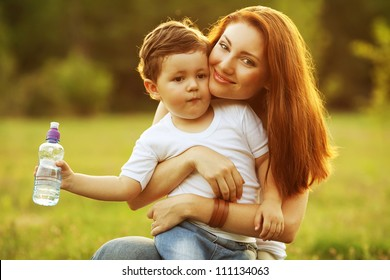 happy family having fun. son holding a bottle of water and mother holding him in her arms. outdoor shot.