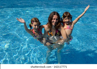 Happy family having fun in swimming pool on summer vacation, smiling mother and kids