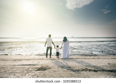 happy family having fun time together at the beach having nice sunset view located in Pantai Remis,Kuala selangor,selangor,malaysia. family concept