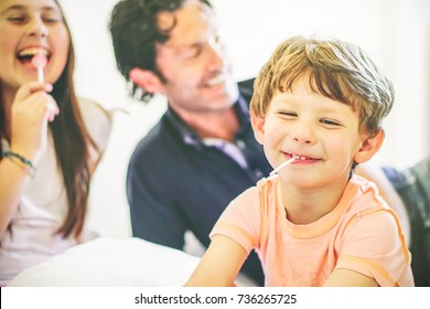 Happy family having fun together on a bed at home - Portrait of a child laughing with lollipop in the living room with his father and sister - Concept of unity, family and love