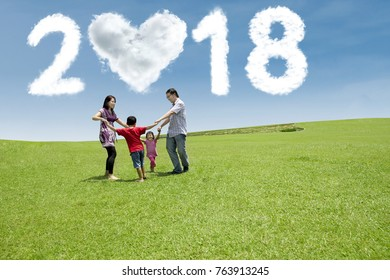 Happy family having fun together in the meadow with clouds shaped numbers 2018 and heart in the sky