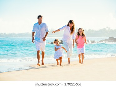 Happy family having fun walking on the beach