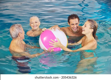Happy family having fun with water ball in swimming pool in summer