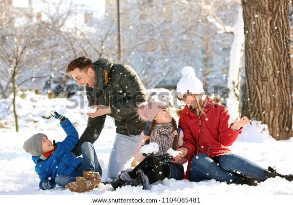 Happy family having fun in winter park