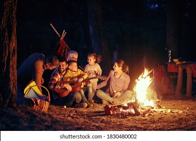 A happy family having a good time around a campfire in the forest in a beautiful night