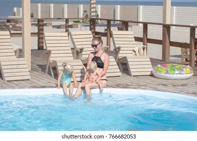 happy family having good time in blue  swimming pool
