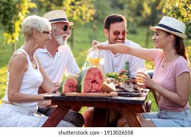 Fröhliche Familie zu Mittag auf der Gartenparty im Sommer. Menschen, Essen, Liebe und Glück Konzept.