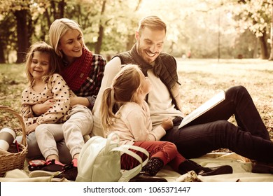 Happy family having picnic. Father teaching daughter to read.