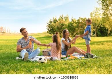 Happy family having picnic in park on sunny summer day