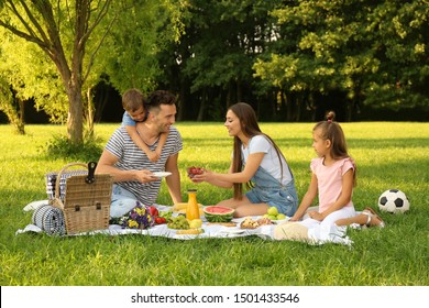 Happy family having picnic in park on sunny summer day