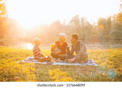 A happy family is having picnic together near a lake in the middle of a park.