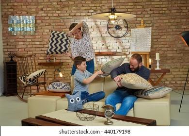 Happy family having pillow fight at home, having fun.
