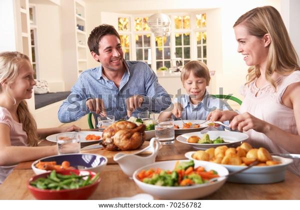 Šťastná rodina s pečenou kuřecí večeři u stolu