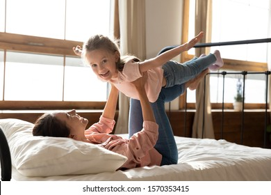 Happy family healthy cheerful young mum lifting cute little child daughter up playing plane doing gymnastic exercise in bedroom, funny kid girl flying in mothers arms look at camera having fun on bed