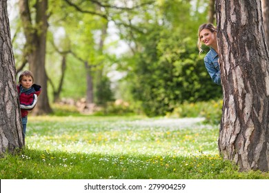 Happy family hiding behind trees while playing in a park