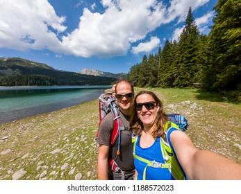 Happy family hiking along beautiful forest lake.