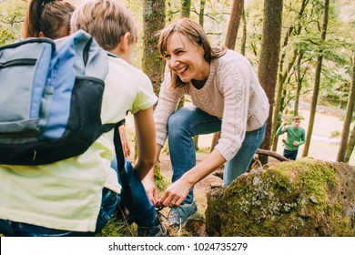Happy family are hiking through the woodlands together. The mother has stopped to help her son tie the laces on his hiking boots.