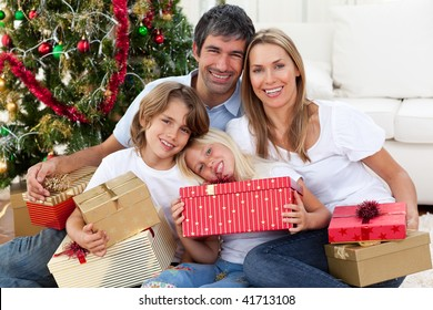 Happy family holding Christmas gifts and sitting on the floor