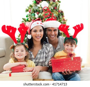 Happy family holding Christmas gifts at home