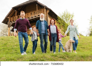 happy family holding hands together while running near country house in village