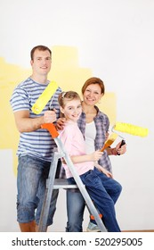 Happy family holding paint rollers looking at camera.