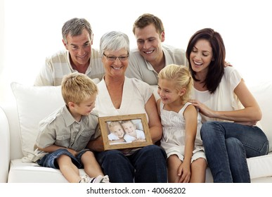 Happy family holding a portrait of children sitting on sofa at home