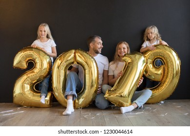 Happy family holding sign 2019 made of golden balloons for new year on black background.