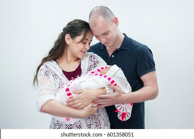 Happy family holding their newborn baby in her arms