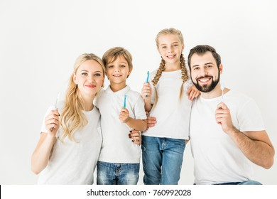 happy family holding toothbrushes and smiling at camera isolated on white