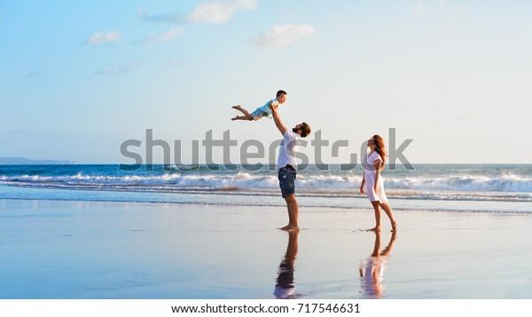 家族のお祝い。黒い砂浜で夕焼けの海波の端を楽しみながら、父と母と子とが歩く。子どもとの夏休みに、親や人の野外活動が盛り上がる。