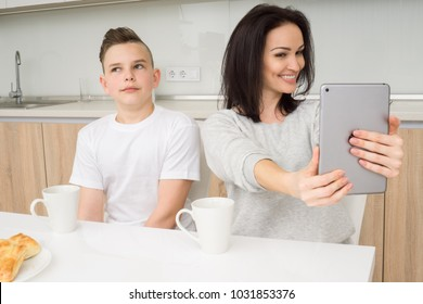 Happy family at home. Beautiful woman with her son taking a selfie photo by tablet