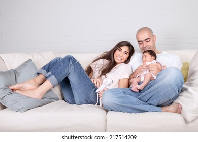 Happy family at home, cheerful young parents with cute newborn baby sitting on sofa in living room, happiness and love concept