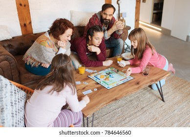 Happy family at home in the couch playing classic table games