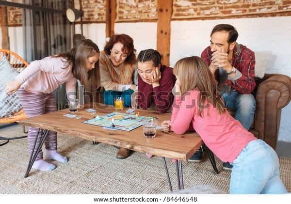 Счастливая семья дома на диване играет в классические настольные игры