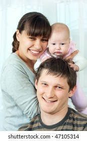 happy family home: father, mother and baby sitting against the window