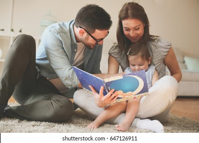 Happy family at home. Little baby sitting on mother lap. Mother and father reading their daughter book story.