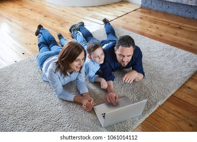 Happy family at home looking at laptop.
