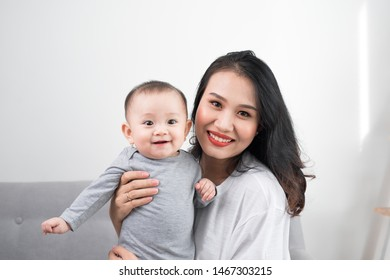 happy family at home. Mother holding baby daughter in living room in cozy weekend morning