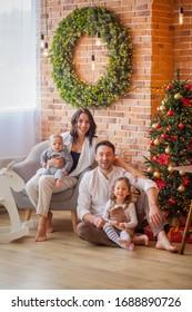 happy family at home near christmas tree new year