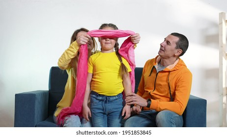 happy family at home. parents and child a playing blindfold game. happy family playing together at home. mom dad and daughter play blindfold game. kid dream happy family fun together at home concept