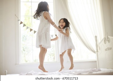 happy family at home. sisters jumping on the bed, playing and laughing