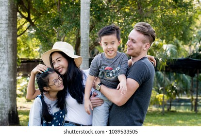 Happy family hugging,enjoying and playing together in nature,Father carrying his son and their family have spending time together at public park, Parents playing with their daughters and son at park,