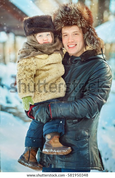 A happy family hugs on the street in winter. Village style. Warm clothes national Russia. Retro fur coat and fur hats. Dad and son smiling