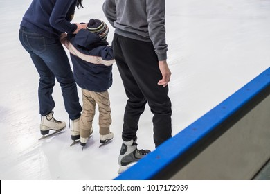Happy family indoor ice skating at rink. Winter activities