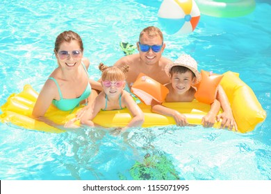 Happy family with inflatable mattress in swimming pool
