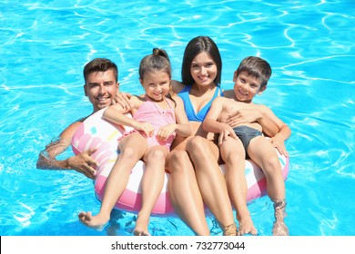 Happy family with inflatable ring relaxing in swimming pool