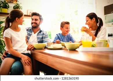 Happy family interacting while having breakfast
