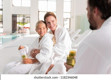 Happy family. Joyful nice mother and daughter looking at the father while sitting together in the spa salon